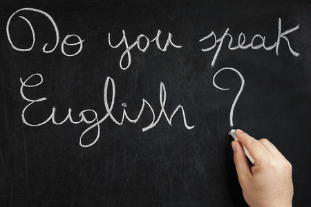Do you speak English question handwritten on used chalkboard by male hand holding white chalk