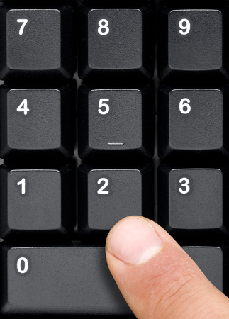 Top view of black computer keyboard numeric keys that are about to be pressed by male finger Banque d'images