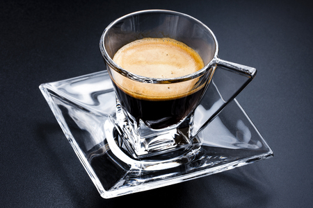 Glass cup of espresso coffee with glass saucer on black