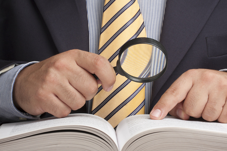 Closeup of businessman holding magnifying glass and looking for information Stock Photo