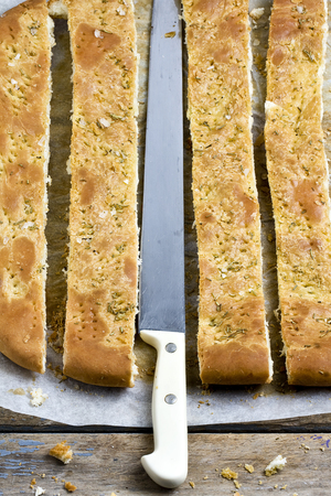 Top view of sliced foccacia bread with rosemary and knife in the middle on wooden rustic table