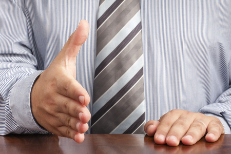 Closeup of businessman sitting at desk and offering hand for handshaking