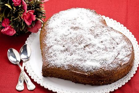 Gâteau au chocolat en forme de coeur sur nappe rouge avec deux petites cuillères d'argent croisées et bouquet