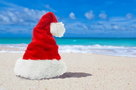 Red Xmas or christmas Santa Hat on paradise beach