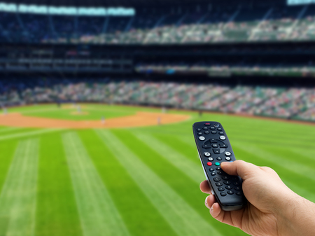 Hand holding remote control on baseball match TV or television