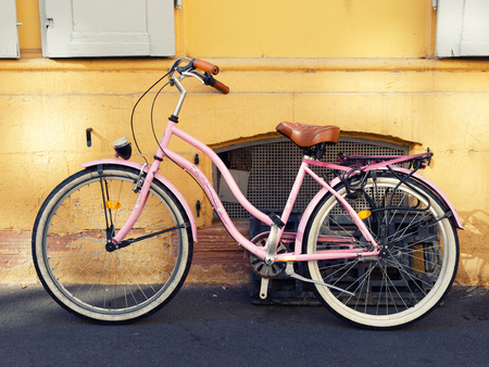 Old pink bicycle on the wall of the street