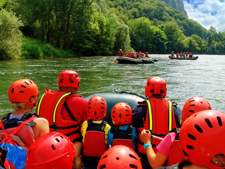 Group of tourists having fun doing water rafting point of view shot