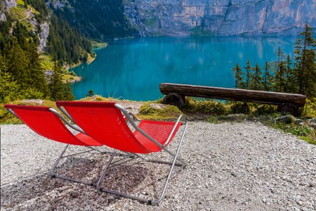 Vacant deckchairs at mountain lake at summer relaxing view