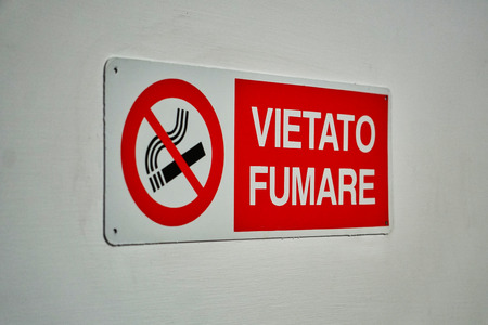 Vietato Fumare (translated Smoking is forbidden) sign on white wall perspective view