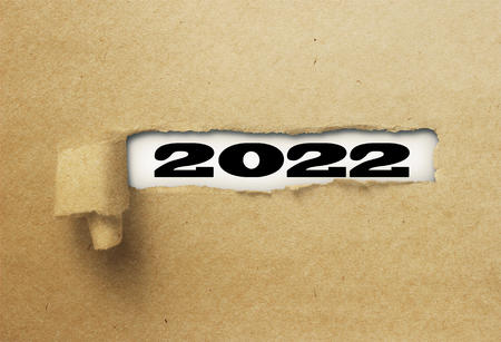 ripped or torn paper revealing new year 2022 on white background