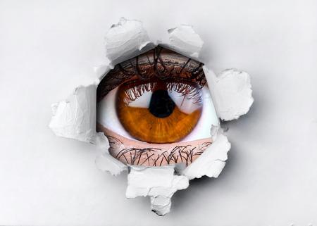Occhio marrone della donna che guarda attraverso il foro in carta strappata