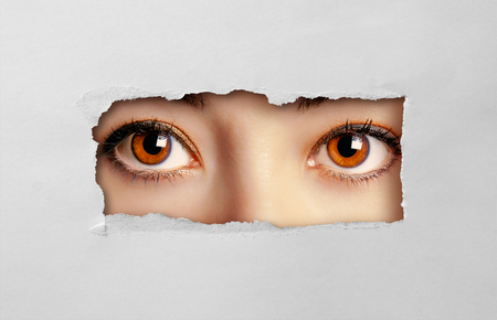 Beautiful female eyes looking through a hole on cardboard Standard-Bild