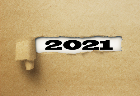ripped or torn paper revealing new year 2021 on white background