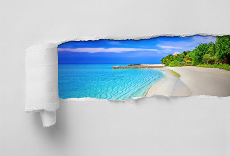 Paper Ripped revealing paradisiac tropical sea and beach vacation destination