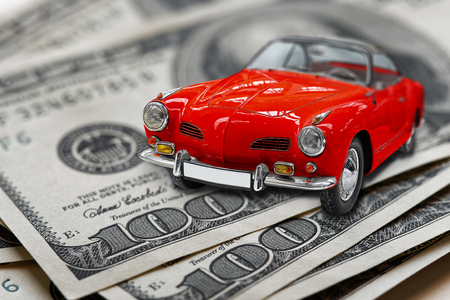 Red toy vintage car on usa or us banknotes closeup