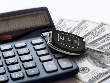 Market car concept. Modern key car on calculator and 100 money dollars bills or banknotes Standard-Bild