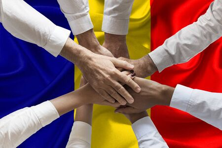 Union or Team Hands multcultural people team over romanian flag topview