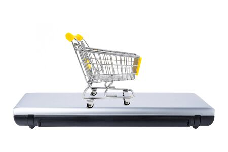 Shopping cart on closed laptop isolated on white. Electronic commerce concept