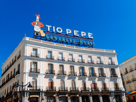 Madrid, Spain - May 2019: Tio Pepe famous brand of Sherry sign on the top of historical building in Puerta del Sol Editorial