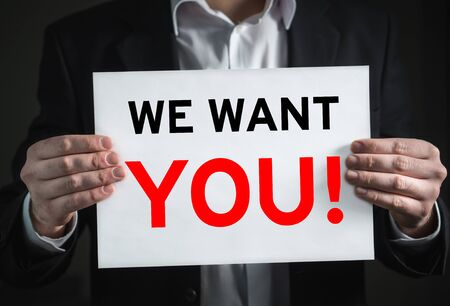 We want you on white card held by businessman closeup