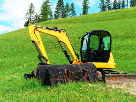 excavator machine in the field at summer Stock Photo