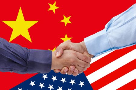 businessmen handshaking on Usa or American and China flags merged politic and economic relationships concept Reklamní fotografie