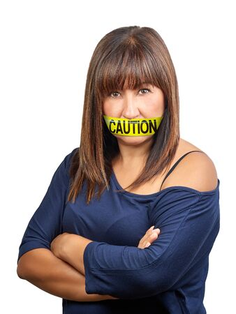 Angry brunette woman arm crossed with yellow caution tape on her mouth to shut and prevent she speaks her mind. Self control concept