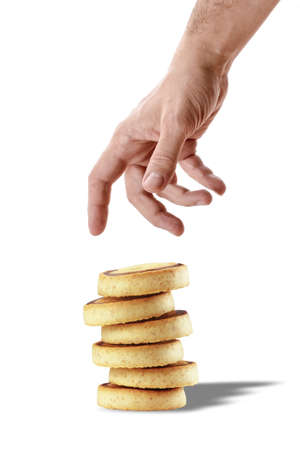 Male hand is going to pick stack of chocolate biscuits or cookies