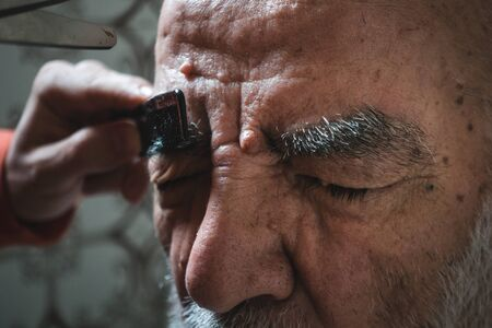 Very old 80 years old Man Getting His Eyebrow Trimmed in Bathroom