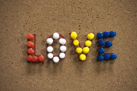 Colorful Love text written with thumbtacks on cork board on a white plain seen in top down view. Usable for valentine's day.