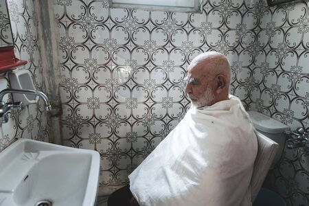 Very Old, White Haired, Bald Man waits for his Haircut In Old Vintage retro style tiled Bathroom