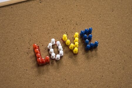 Colorful Love text written with thumbtacks on cork board. Usable love text for valentine's day.