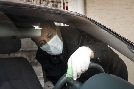 Middle aged Turkish man disinfects his car's steering wheel as a precaution for the pandemic corona virus Фото со стока