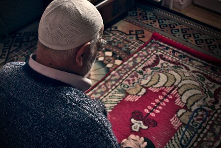 Very old bearded Turkish muslim male at his 80's wearing a prayer cap doing Salah prayer at his home on his prayer rug in Ramadan month