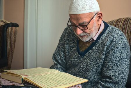 Elderly Turkish muslim male reciting the holy book of Islam, Qur'an in Ramadan month before iftar