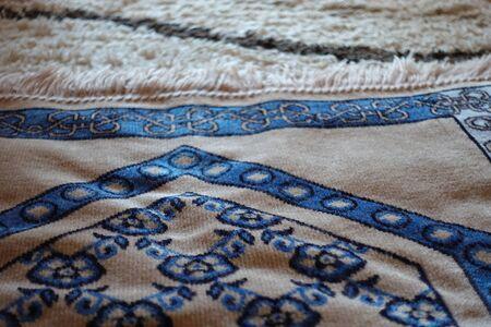 Close up shot of beautiful blue islamic prayer rug on turkish carpet on a sunny day