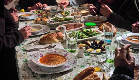 Crowded Turkish Muslim family having iftar together in happiness with delicious vegan food on the table Foto de archivo