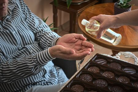 Close up Turkish Muslim housewife serving chocolate and cologne to her husband to traditionally celebrate eid ul fitr(sugar feast) after the end of the holy month Ramadan