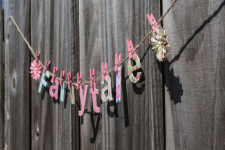 The word  Fairytale  hanging on a string against a fence