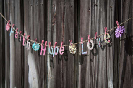 hope: The words  Faith Hope Love  hanging on a string against a fence