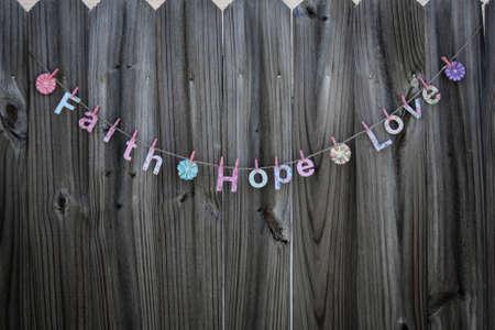 geloof hoop liefde: De woorden Faith Hope Love opknoping op een string tegen een hek Stockfoto