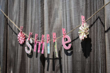 The word  Smile  hanging on a string against a fence