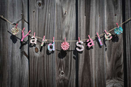 The words  Yard Sale  hanging on a string against a fence Stok Fotoğraf