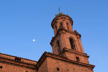 The moon appears over the bell tower