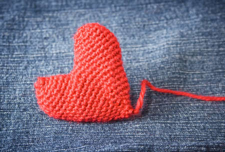 Knitted heart on blue jeans texture  photo