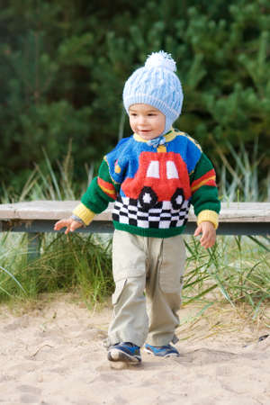 2 year old: Walking boy in knitted sweater and hat