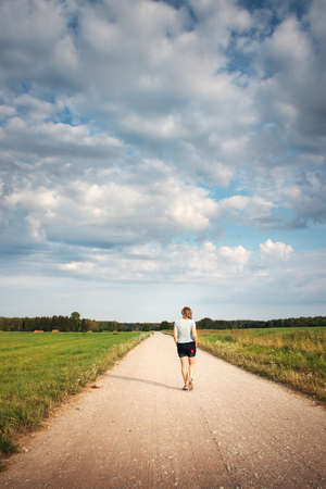 Woman walking on the country road photo