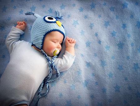 4 maanden oude baby in uil hoed slapen op blauwe deken Stockfoto