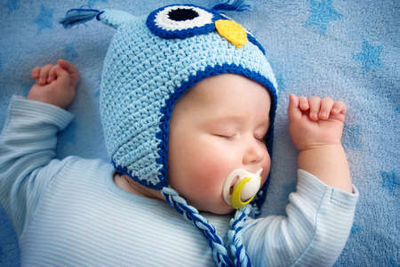 青い毛布で寝ているフクロウ帽子で生後 4 ヶ月の赤ちゃん