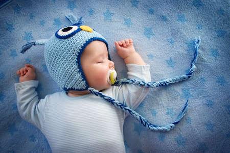 enfant qui dort: 4 mois vieux bébé dans hibou dormir sur une couverture bleue Banque d'images